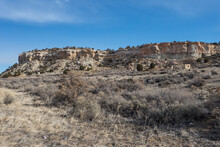 Bushes And Grass Make Up A Dry Desert Landscape With Rocky Mountainside On Clear Day In Rural New Mexico