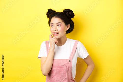 Fotografia, Obraz Pensive asian girl feeling excited, biting fingernail and looking left thoughtfu