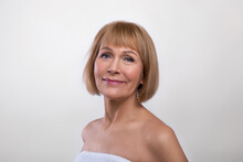 Aging Gracefully. Beauty Portrait Of Senior Lady Wearing Towel, Having Silky Skin, Looking At Camera On Light Background