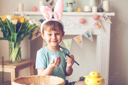 Obraz Easter. A little boy is painting Easter eggs. Easter decor. - fototapety do salonu