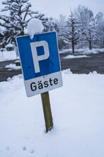 A Snowy Guest Parking Sign.