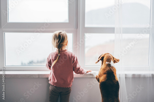 Tablou Canvas Dog and baby girl staring out a large window.