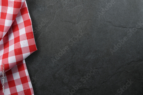 Classic italian cooking background - red checkered tablecloth on a vintage black stone kitchen countertop with copy space