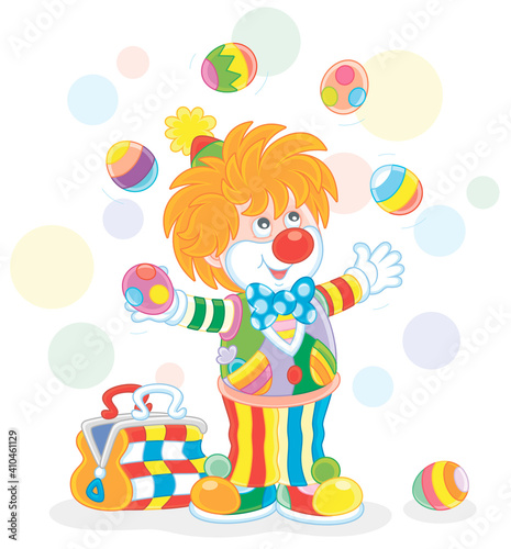 Funny and friendly smiling clown in a colorful comic suit juggling with decorate Fototapeta