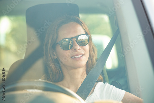 Fototapeta Donna chiara con  occhiali da sole guida un veicolo seduta con la cintura allacc