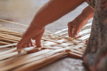 Hand Elderly Woman Are Weave Bamboo Strips Of Bottom Of Basket Close-up.