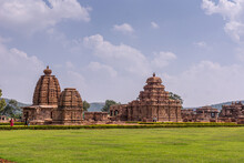 Bagalakote, Karnataka, India - November 7, 2013: Pattadakal Temple Complex. Green Park Landscape With Complex Of Brown Stone Buildings Set Together Under Blue Cloudscape.