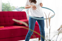 Happy Asian Women Playing Hula Hoop In The Living Room At Home. Young Adult Woman Learning To Play With A Hula-hoop In A Living Room.