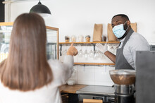 An African-American Male Waiter, Cafe Owner Wearing Mask And Gloves Stands Behind The Counter, A Female Customer Points An Order. A Multiracial Entrepreneur, Bakery Staff During Quarantine Lockdown