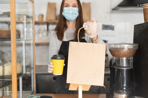 Package with a take away order and paper cup of coffee in hands of waitress, cafe owner, a woman in mask and gloves in out of focus. Protective measures due quarantine lockdown, pick up and go concept © Вадим Пастух