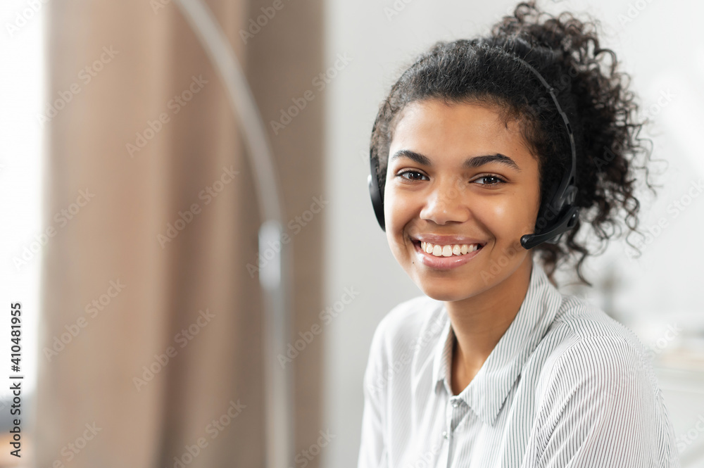 Fototapeta Headshot of friendly charming African American mixed-race woman in headset, smiling at camera working in the customer service department as call center operator, providing consultations on the phone