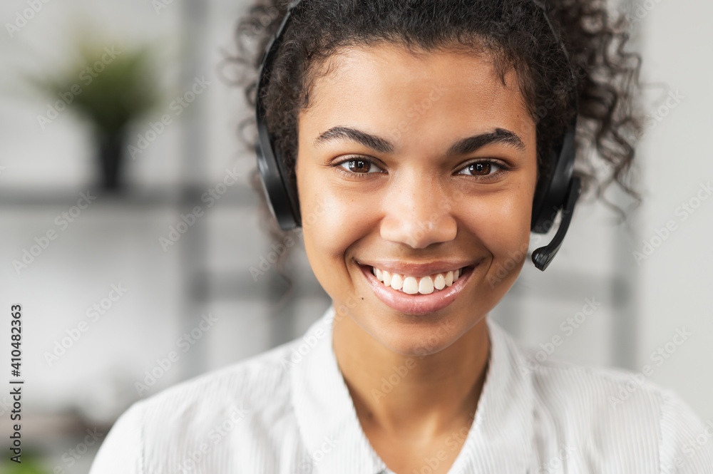 Fototapeta Headshot of friendly African American millennial woman in headset, smiling and working in emergency helpline or in the customer service department as call center operator, helping client with inquiry