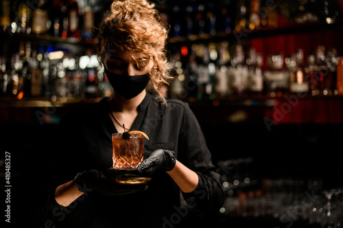view of woman in black mask and black gloves holding glass with cocktail © fesenko