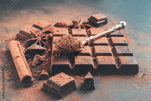 Fototapeta Brown cocoa powder in the spoon on chocolate bar, chopped chocolate cubes on dark background obraz