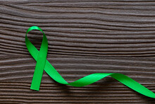 Top View Of Green Color Ribbon On Dark Wooden Background. Gallbladder And Bile Duct Cancer, Mental Health, Perception Of Cerebral Palsy, Organ Donation, World Kidney Day And Environmental Care.