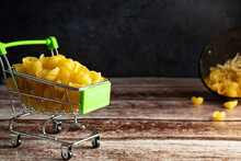 Pasta In A Shopping Trolley, Trolley, On A Dark Background, Pasta With Seashell