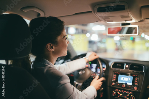 Fotografia Young businesswoman driving her car into public underground garage