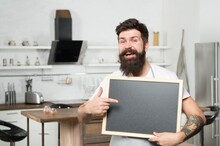 Chalkboard For Advertising. Brutal Hipster Man Holding Blank Board, Copy Space. Job Search. There Are Vacancies. Shopping Sale And Discounts. Chef Menu In Kitchen. Look Over There