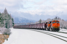 Winter Scene Of Locomotive Pulling Freight Cars Close To Whitefish, Montana With Fresh Snow In The Foreground And Surrounding Foliage.