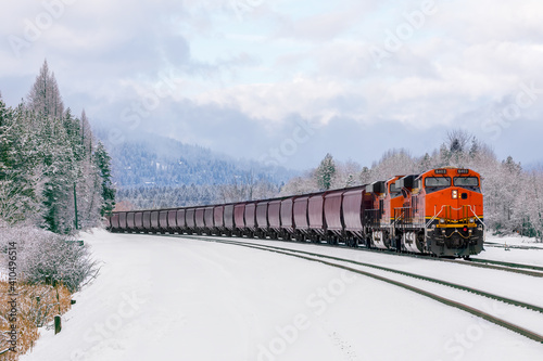 Photo winter scene of locomotive pulling freight cars close to Whitefish, Montana with fresh snow in the foreground and surrounding foliage