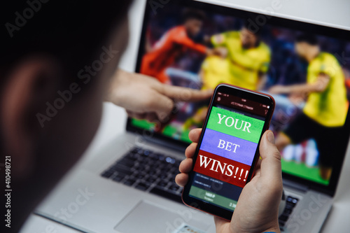 Man watching football online broadcast on his laptop and celebrate victory in betting at bookmaker's website Wallpaper Mural