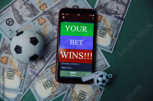 Ball, whistle and smartphone with bet application on cash and green background. Gambling and bet concept. © burdun