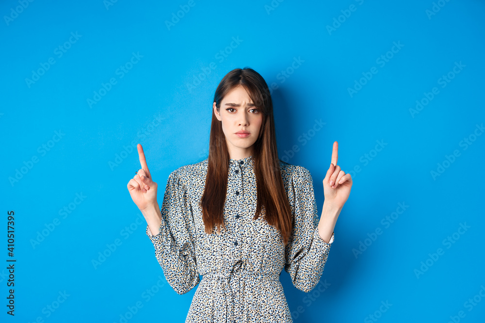 Fototapeta Hesitant and worried young woman frowning, pointing fingers up with sad face, standing on blue background