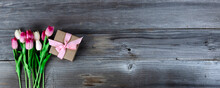 Top View Of Pink Tulips And A Giftbox On Rustic Wood For Mothers Day Concept