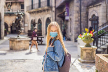 Young Woman Wearing A Medical Mask During COVID-19 Coronavirus Tourist Walks Down The Street In A European City After The End Of COVID-19 Coronavirus. Quarantine