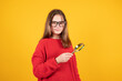 Teen girl holding magnifying glass and looking at something. Young schoolgirl in red sweater and eyeglasses on yellow background with copy space