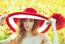 Spring Blossom. Facial Portrait Of Sexy Female Model On Poppy Field With Hat And Poppy Bouquet.