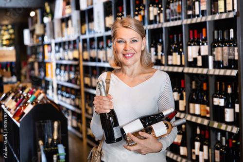 Canvas-taulu Positive glad cheerful mature blonde woman holding in hands bottles with wine pu