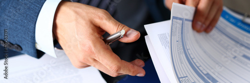 Obraz Male arm in suit offer insurance form clipped to pad and silver pen to sign closeup. Strike a bargain, driver money loss prevention, secure road trip, harmless drive idea, owner protective concept - fototapety do salonu