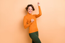 Photo Of Lucky Adorable Young Lady Wear Orange Turtleneck Rising Fists Isolated Beige Color Background