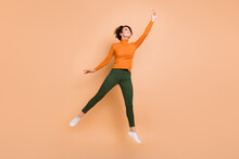 Full Size Photo Of Young Beautiful Happy Positive Smiling Cheerful Girl Jump Look Copyspace Isolated On Beige Color Background