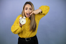 Young Beautiful Blonde Woman With Long Hair Wearing A Yellow Sweater Surprised Holding And Pointing A Clock