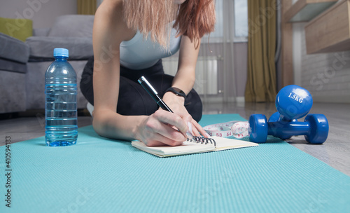 Obraz Young woman sitting in mat writes training plans at home. - fototapety do salonu