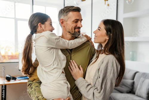 Obraz Happy masculine military man smiling and hugging his family indoors - fototapety do salonu