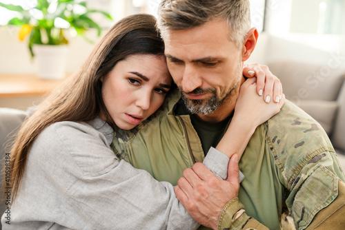 Obraz Unhappy woman hugging her military husband while sitting on sofa - fototapety do salonu