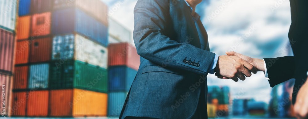Fototapeta export and import business. businessmen handshake at industrial container terminal. maritime transport and logistics concept