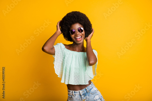 Obraz Photo portrait of woman touching hair isolated on vivid yellow colored background - fototapety do salonu