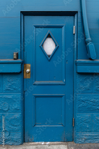 Obraz Vertical shot of blue door against a blue painted wall - fototapety do salonu