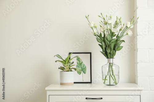 Obraz Decorative vase with flowers and houseplant on commode indoors - fototapety do salonu