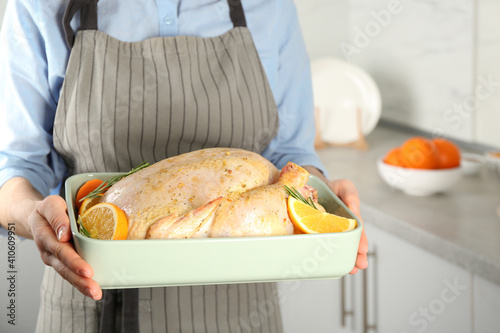 Fototapeta Woman holding pan with raw chicken and oranges in kitchen, closeup