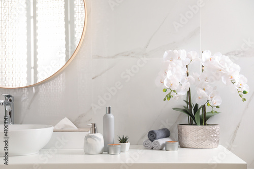 Beautiful flowers, burning candles and different toiletries on countertop in bathroom © New Africa