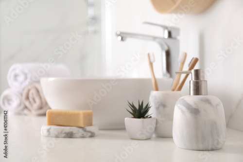 Fotografia Holder with toothbrushes, plant and different toiletries near vessel sink in bat