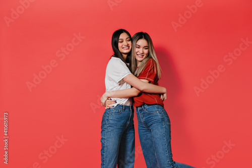 Slika na platnu Women in jeans and t-shirts hugging on isolated background