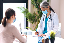 Consultation Of A Doctor Of General Medicine. A Girl At The Doctor's Appointment At The Clinic, The Doctor Prescribes Treatment. Medical Care, Health Concept
