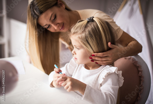 Obraz Mother and daughter in bedroom. Little girl drawing. - fototapety do salonu