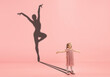 Childhood and dream about big and famous future. Conceptual image with girl and drawned shadow of female ballet dancer on coral pink background. Childhood, dreams, imagination, education concept.